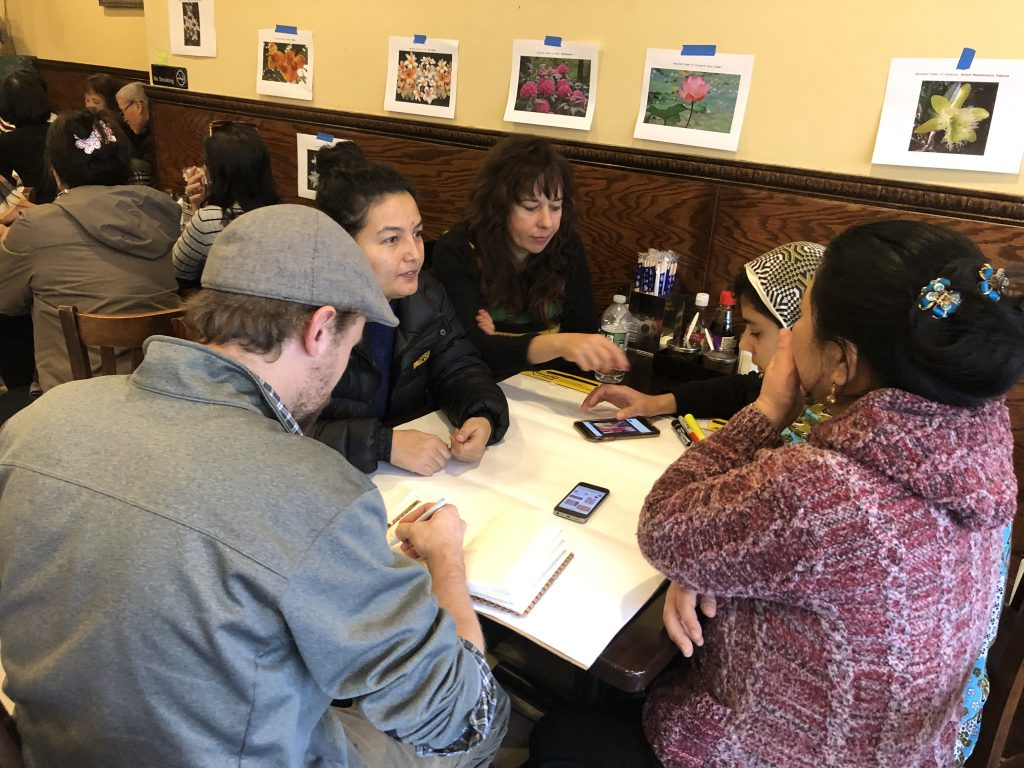 A crowded group of people sits and talks at a table inside a restaurant with pieces of paper in front of them. On the walls, there are taped printouts showing different flowers.